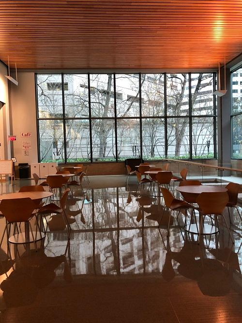 Photo of the Bonneville Power Administration cafe dining area dim and deserted. The highly polished floor reflects the empty tables and chairs. Tall paned windows overlook a lonely gray landscape of buildings and stark branched trees.