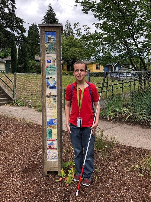 Photo of OCB SWEP student Daniel Bair standing outside by a vertical art mosaic made by students of James John Elementary.