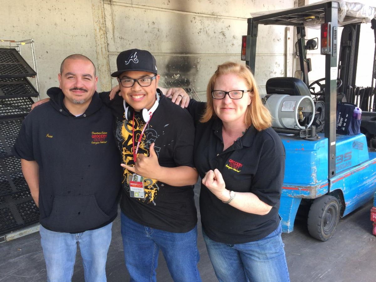 Photo of a smiling young man giving the hang loose sign to the camera. He stands between two smiling Grocery Outlet employees in front of a forklift. One employee gives the camera a we-did-it fist-pump.