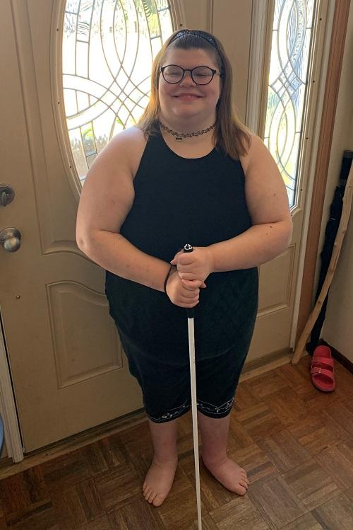 CJ stands at her front door in her interview clothes with her white-tipped cane, smiling