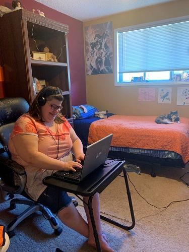 Smiling SWEP student CJ in her bedroom on her laptop at her desk. She is wearing headphones and typing. In the background there is a neatly made bed and a calico cat curled up on the quilt.