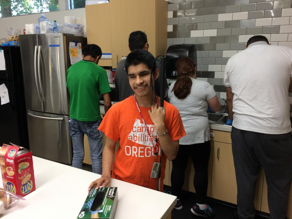 Picture of a smiling young man in an orange Camp Abilities Oregon shirt. He holds a white cane and stands at the island of a spacious brightly-lit kitchen. Behind him other students and instructors do food prep.