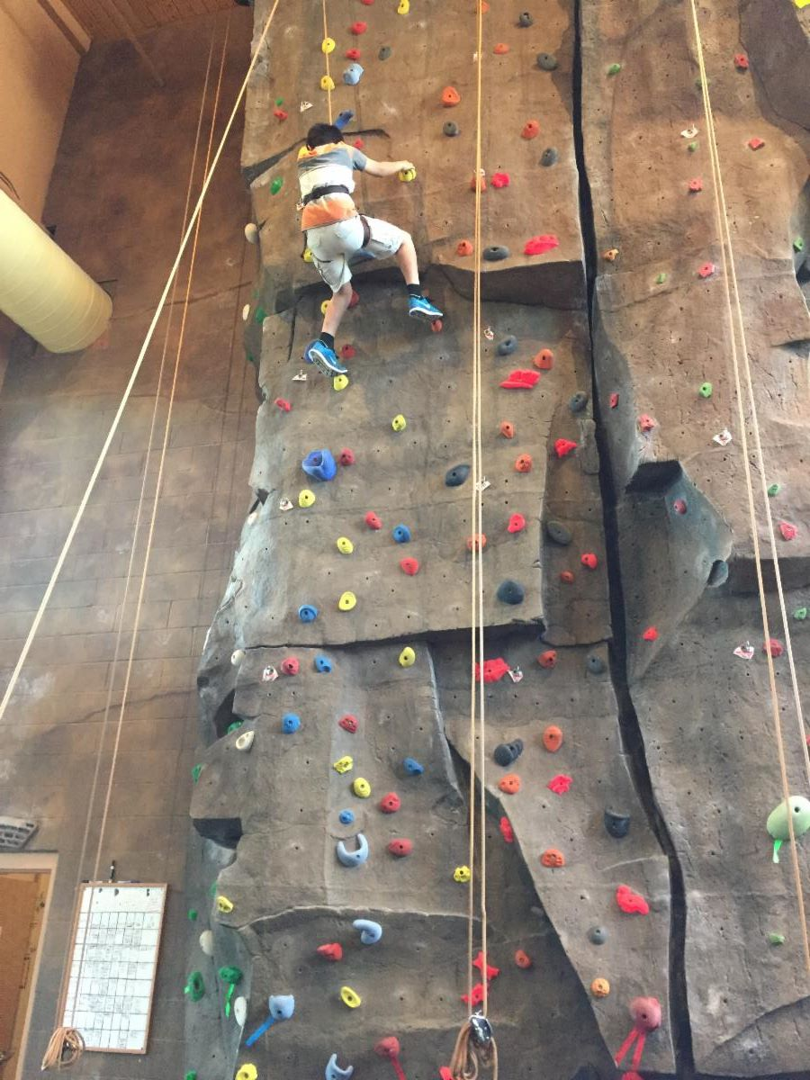 Picture of a SWEP student climbing a three-story rock wall. He is near the top. He is attached to the steep rock face by safety ropes.