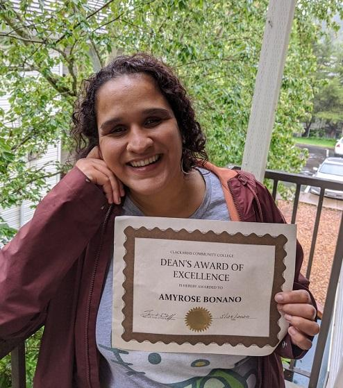 Photo of smiling AmyRose holding up her Dean's Award of Excellence certificate.