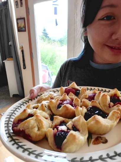 SWEP student proudly holding out plate of berry pastries she cooked.