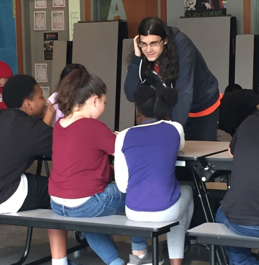 Picture of a young man leaning over a table towards several children he is instructing.