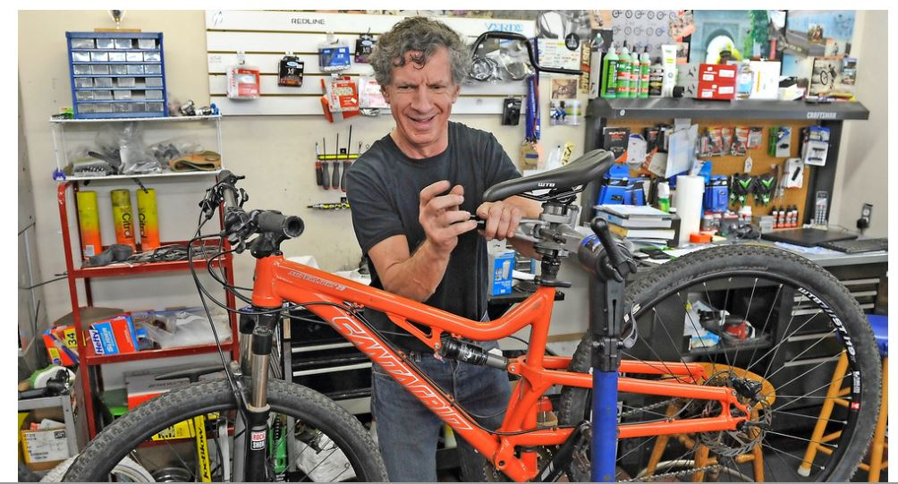 Photo of former OCB client Stan Moore fixing a bike in his Medford Bike Shop. Photo from Mail Tribune.