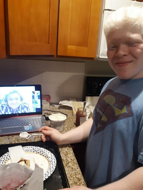 SWEP student KC standing at kitchen counter smiling. Cooking ingredients and a laptop displaying the face of a smiling cooking teacher on a Zoom meeting are seen next to him.