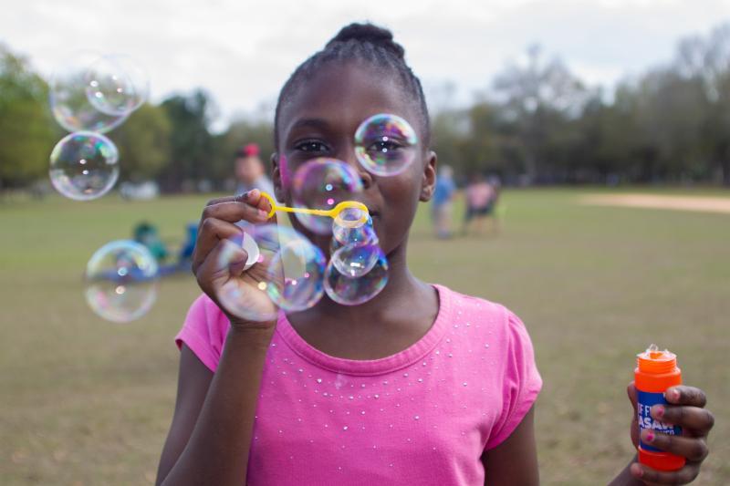 Una niña haciendo burbujas en un parque
