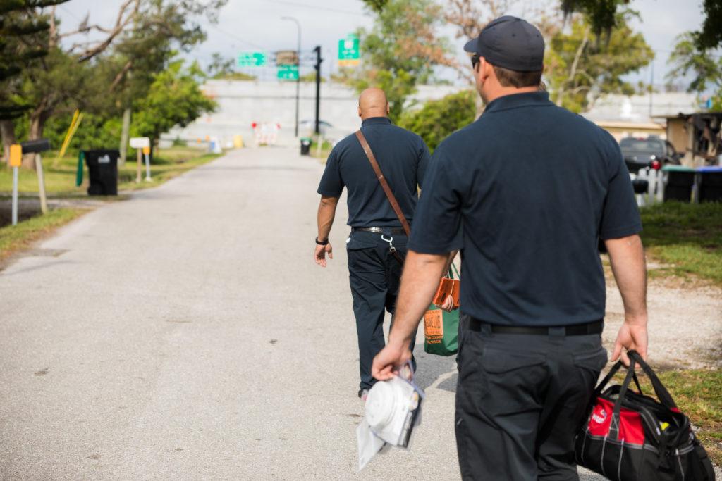 Two men carrying work bags walking down a neighborhood street