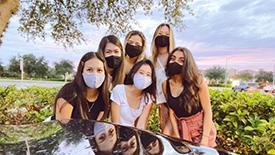 Six young women wearing masks