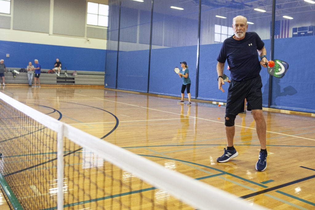 A man in an inside gymnasium hitting a ball with a paddle