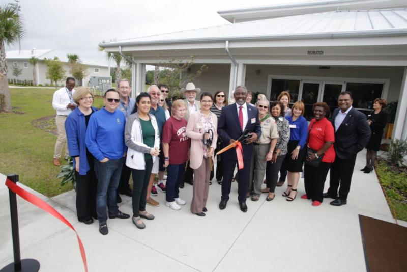 Mayor Demings, Commissioner Bonilla, Commissioner Gomez Cordero are joined by a dozen other individuals. They are standing for a photo and the Mayor is holding large scissors which he used to cut a ribbon.
