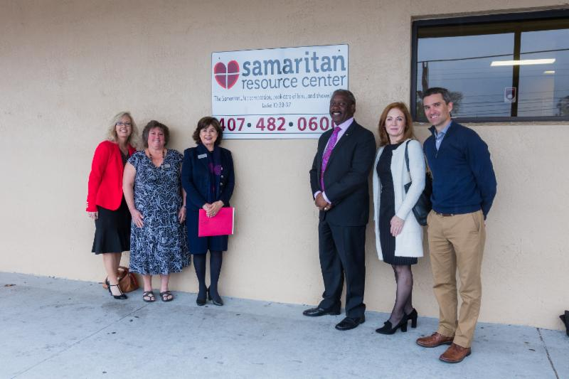 Mayor Demings and four other individuals stand by the Samaritan Resource Center sign.