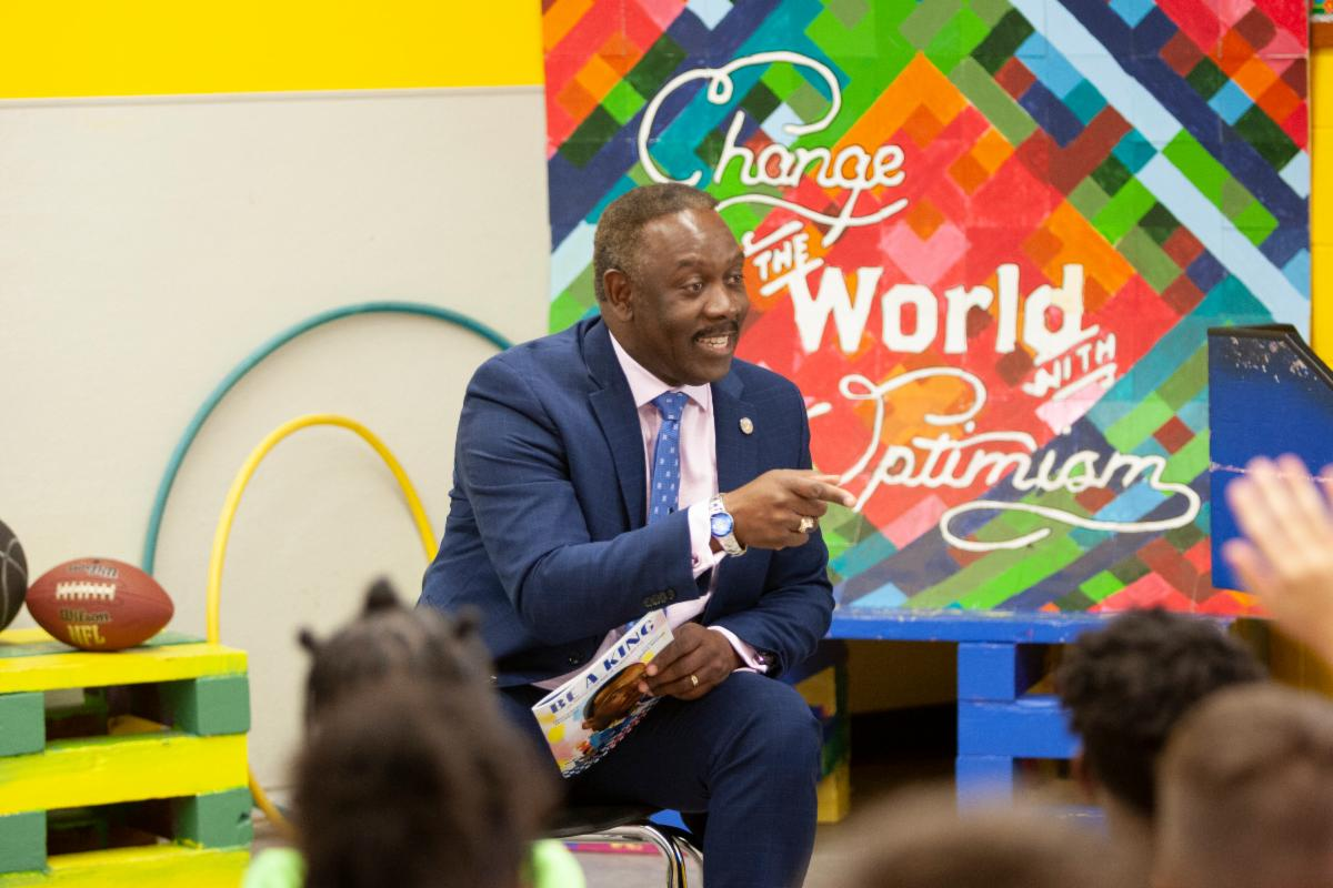 """Mayor Demings reading to children. Behind him, the words """"Change the World with Optimism."""""""