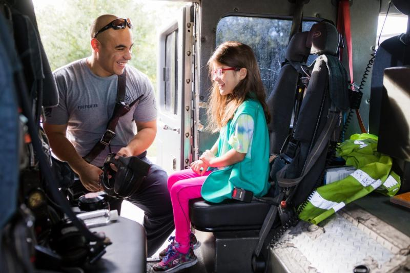 Firefighter chatting with a young girl