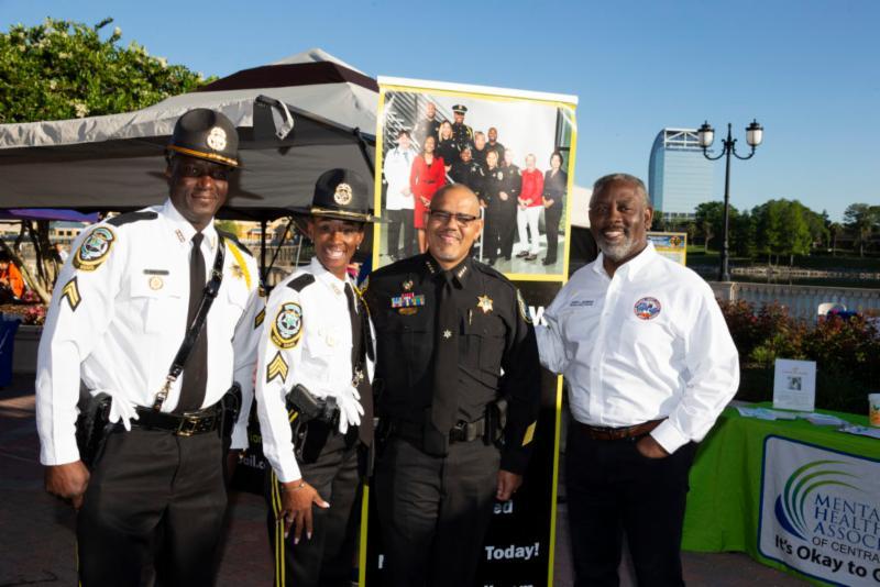 Los oficiales de Correccionales del Condado de Orange, el Jefe de Correccionales del Condado de Orange, Louis A. Quiñones, y el Alcalde del Condado de Orange, Jerry L. Demings, parados afuera durante el evento NAMIWalks Greater Orlando.
