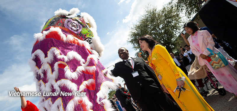 Mayor Demings stands alongside Vietnamese Lunar New Year Parade attendees while smiling and extending his hand towards a tall, colorful sequin and feather decorated Dragon.
