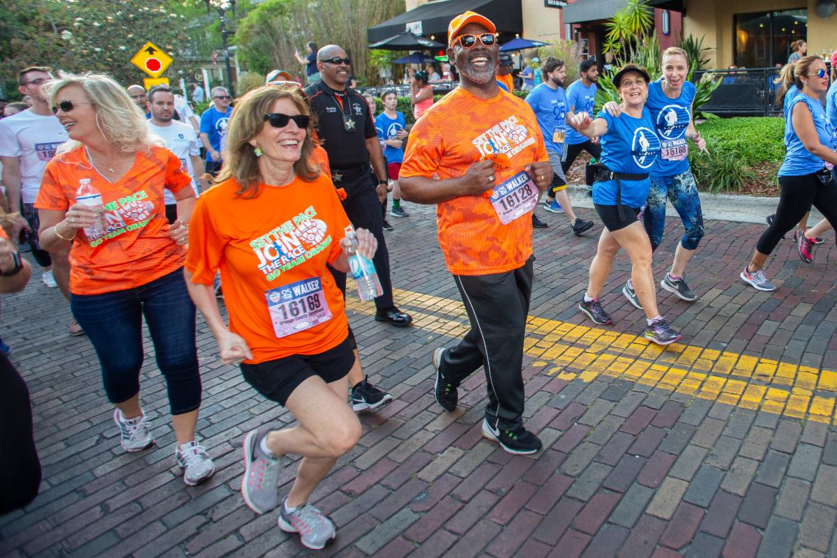 Mayor Demings and staff are smiling as they run on a cobblestone road