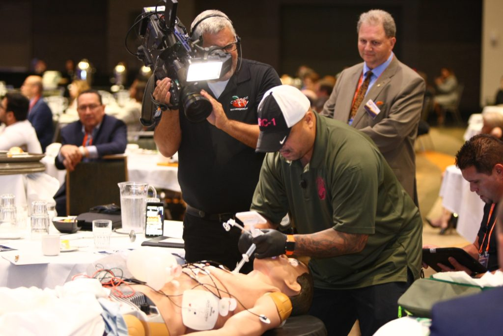 Video cameras record a demonstration of a patient being aided by medical technicians with the help of augmented reality technology