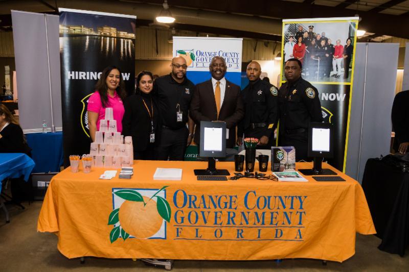 El Alcalde Demings junto al personal del Condado en el puesto del Condado de Orange durante la Feria de Empleo del Alcalde.