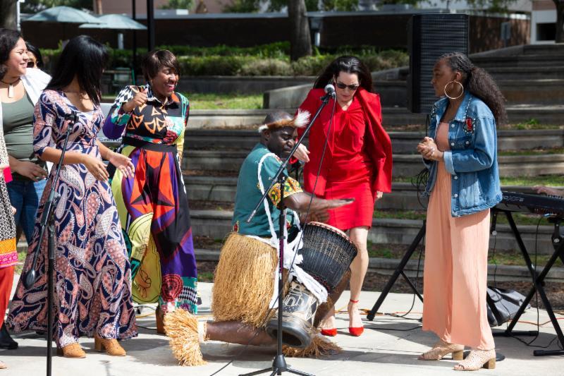 Artistas actuando en el escenario al aire libre. Hay bailarinas y un percusionista junto con las cantantes.