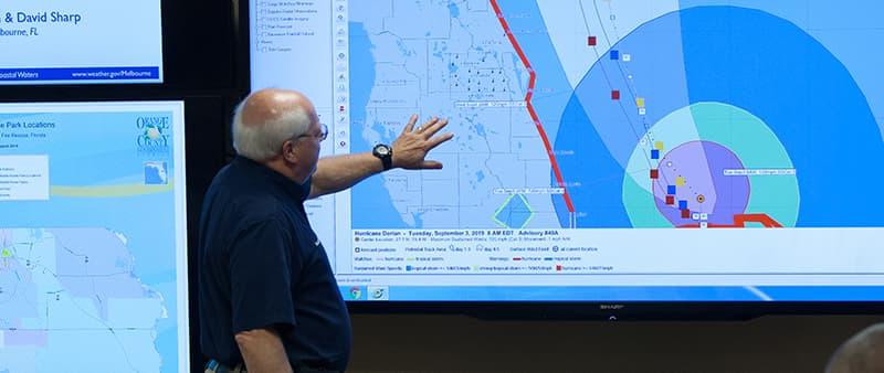 Gerente de la oficina de manejo de emergencias Kieth Kotch apuntando a una pantalla que muestra el mapa del huracán Dorian