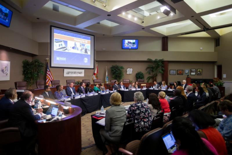 Inside of the brightly lit Board of County Commissioners Chambers the Housing for All Task Force members sit in front of the dais at tables arranged in an oval shape as they discuss the items on the agenda. Individuals from the public are seated in rows.