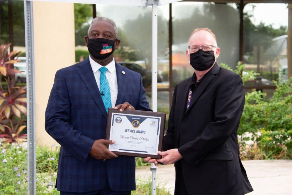 LinkedIn Post - Mayor Demings handing an employee a service award plaque