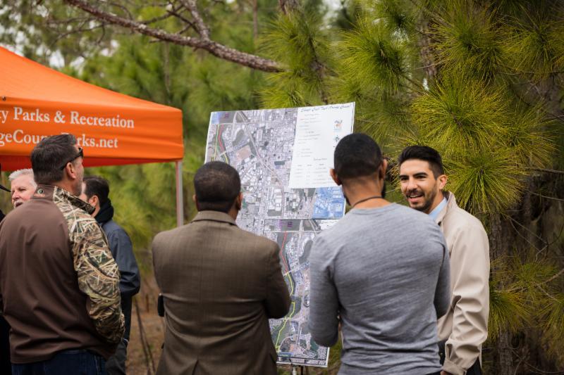 Cuatro residentes y líderes de la comunidad, todos hombres, parados frente a un mapa gigante. Están afuera en un día nublado.