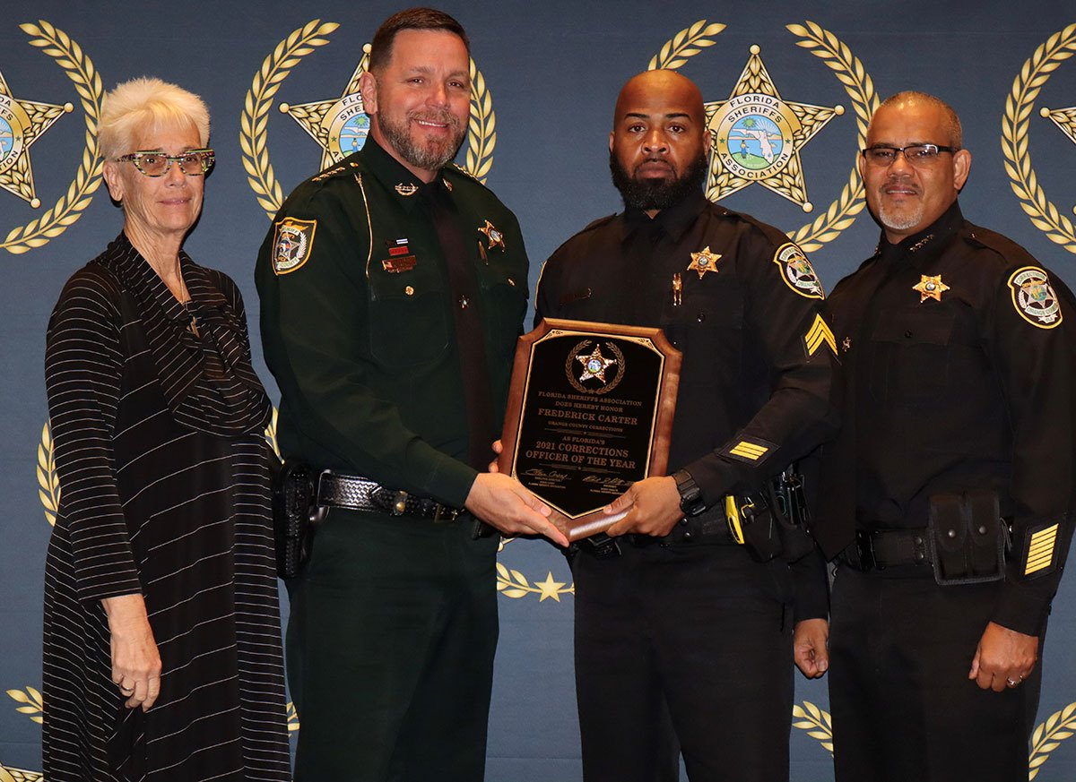 Four officers holding a plaque