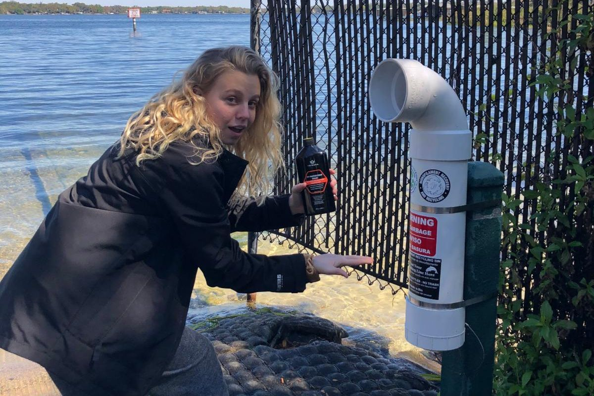 A young woman pointing to a garbage bin near a lake
