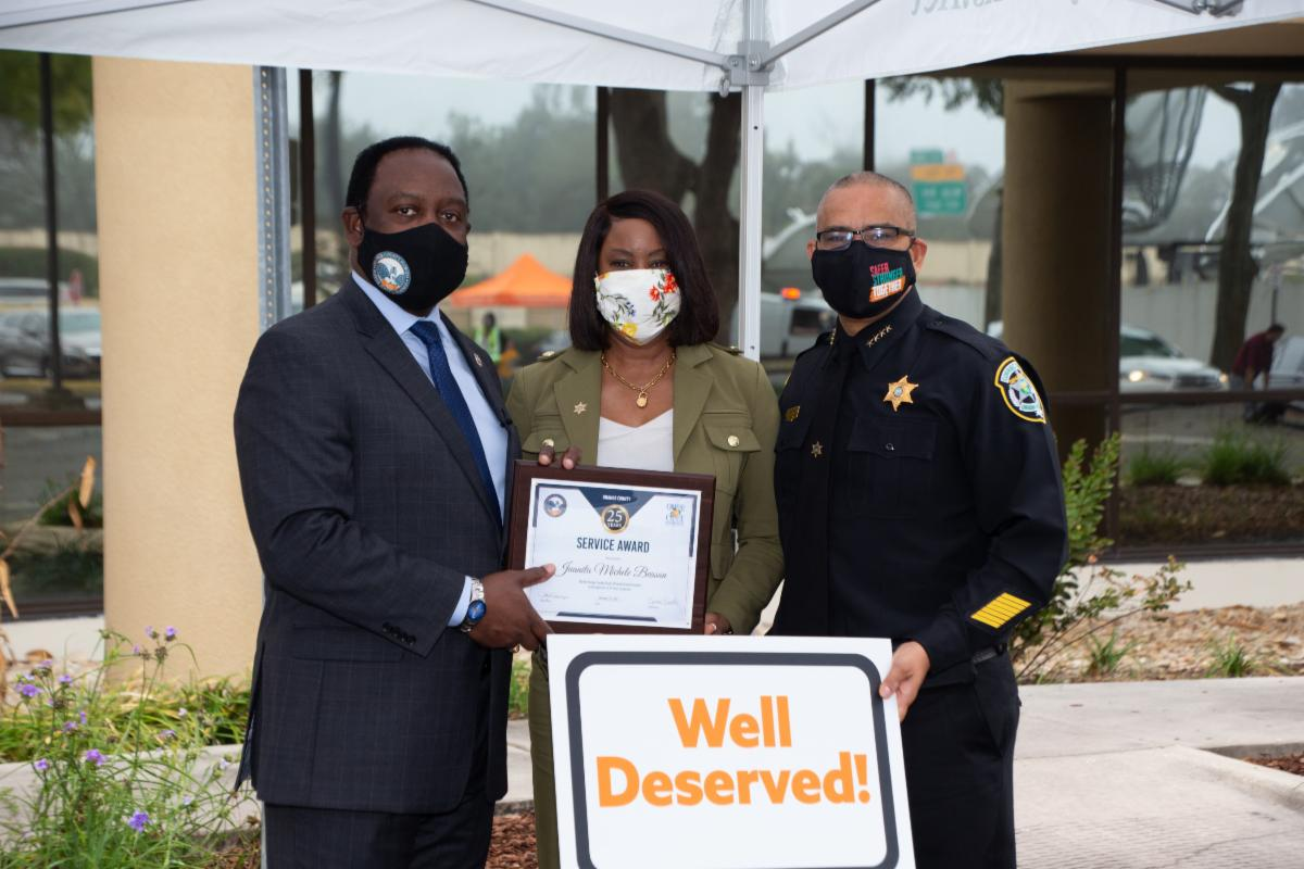 Mayor Demings and an employee with an award