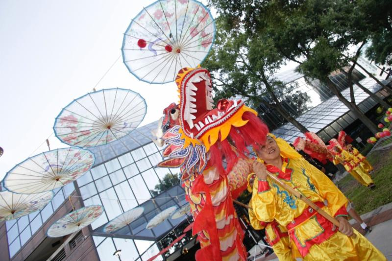 A man in traditional red and yellow garb is leading a dance with a decorative dragon