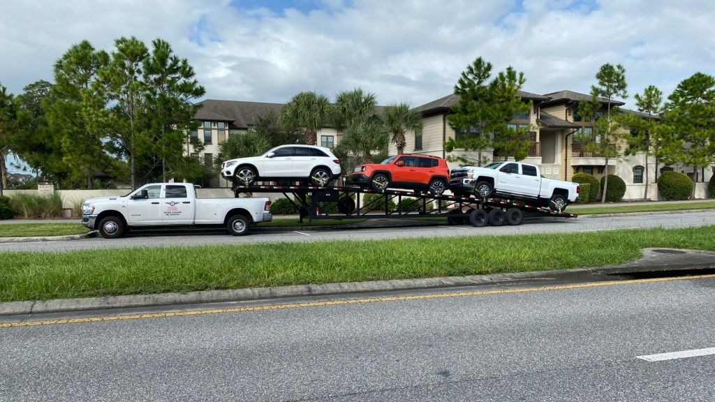 Large truck carrying three vehicles parked on the side of the road