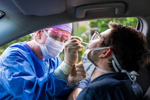 Healthcare worker administering a nasal swab test to a man in his car