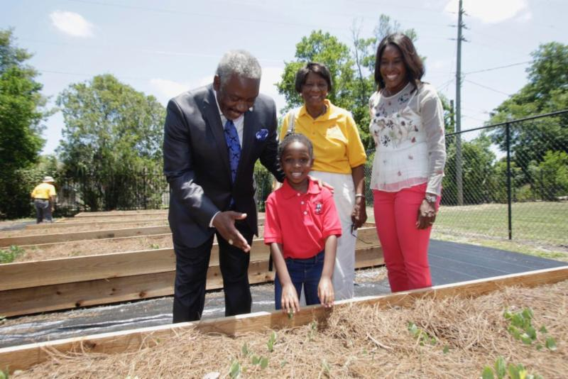 Mayor Demings and a child at a community garden. Commissioner Siplin and another woman smile in the background.