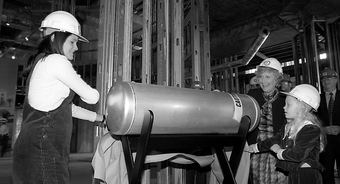 A greyscale photo of a large tank time capsule being held by a child