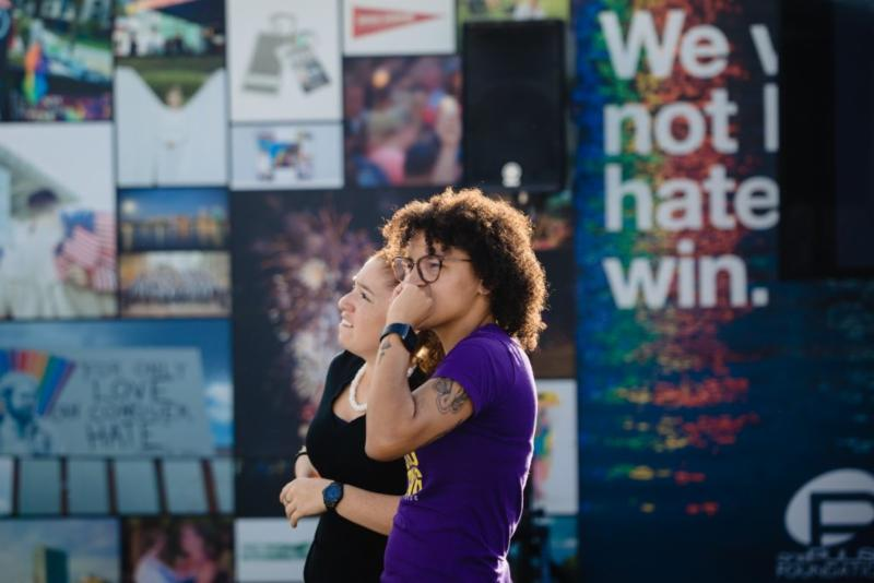 Two people stand in front of the Pulse memorial as they contemplate the artwork on display.