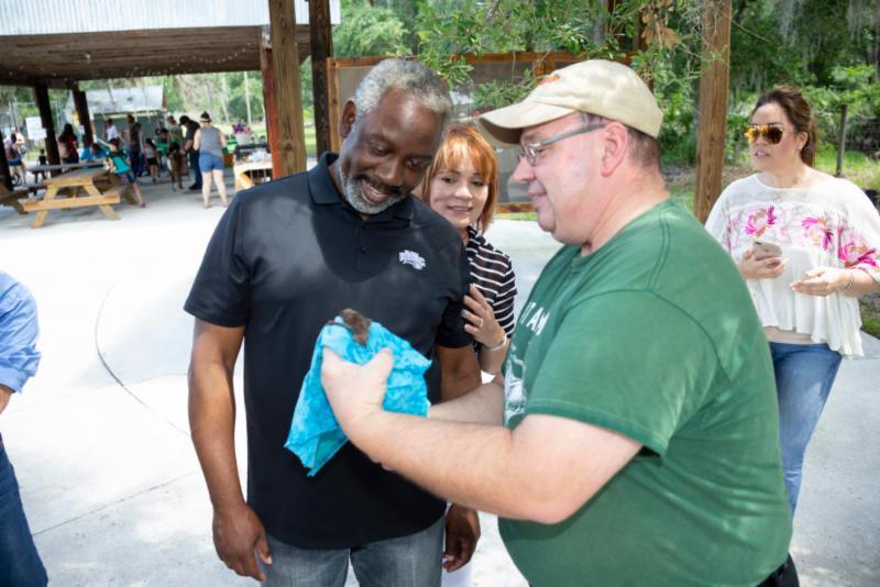 El Alcalde Demings observa a una cría de murciélago mientras la Comisionada Gomez Cordero, que se encuentra parada detrás de él, mira por encima de su hombro.