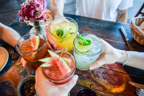 Friends toasting_ saying cheers holding tropical blended fruit margaritas.  Watermelon and passionfruit drinks.