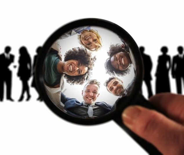 magnifying glass to look closely at silhouetted crowd reveals smiling faces in color