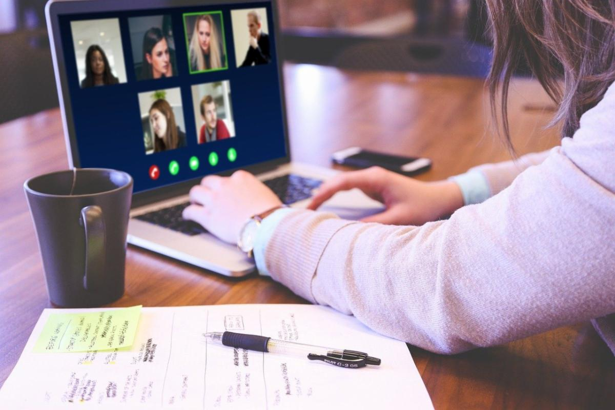 young woman in pink uses laptop for video conference with 6 others