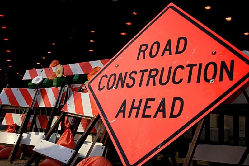 Road Construction Ahead sign with numerous barricades