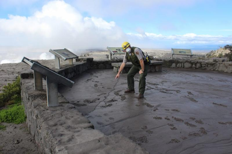 A National Park Service staff points to the crack in the ground surface at the scenic overlook for the Kilauea crater.