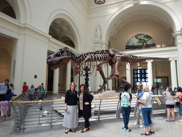 Two women pose in the large museum gallery in front of the Tyrannosaurus skeleton on display.