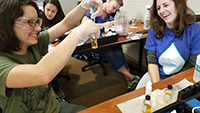 Females smiling and demonstrating water quality testing using a test tube.