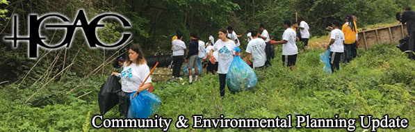 Volunteers with trash bags in a grassy area