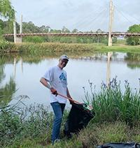 Man picking up trash in front of waterbody