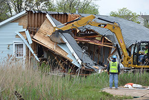 A portion of roof is removed with a claw during demolition of a home swept from its foundation into a marsh in Union Beach. The project falls under FEMA's Public Assistance Waterways Debris Removal Program. Photo by Sharon Karr-FEMA